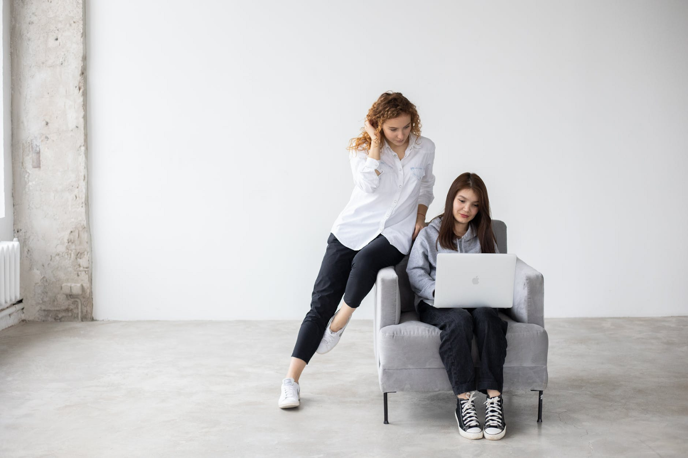 A teen works on her laptop; her mom sits next to her. #parenting #teens #school #education #family #mom