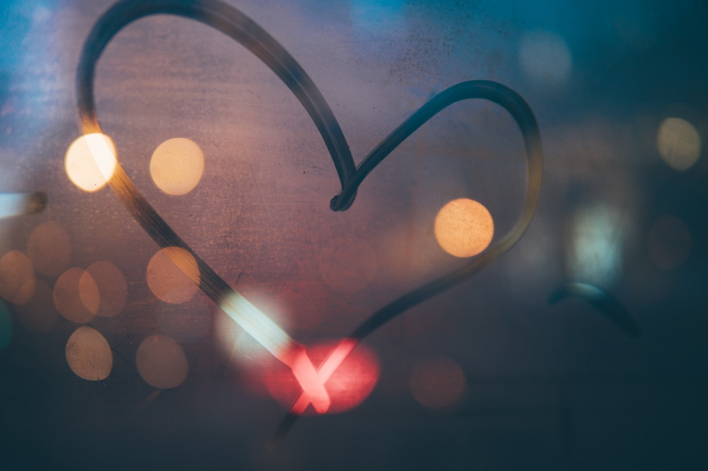 A closeup of a heart drawn on a foggy window, with blurred lights in the background