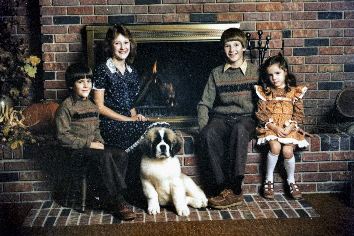 Four kids and a dog sitting by fireplace