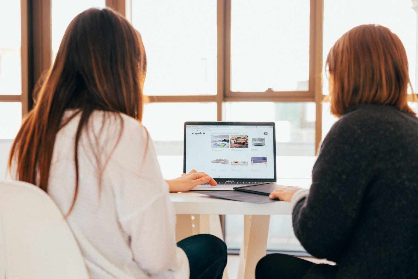 Two girls sitting at a table looking at a laptop