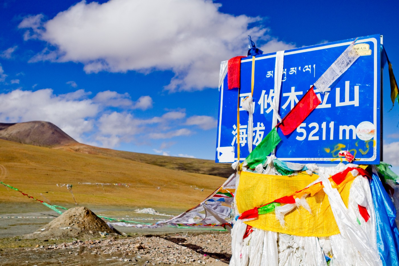 A mountain plateau. A road sign indicating elevation is wrapped around Tibetan prayer flags. The sign is mostly written in Chinese characters, but there are smaller Tibetan characters above it.
