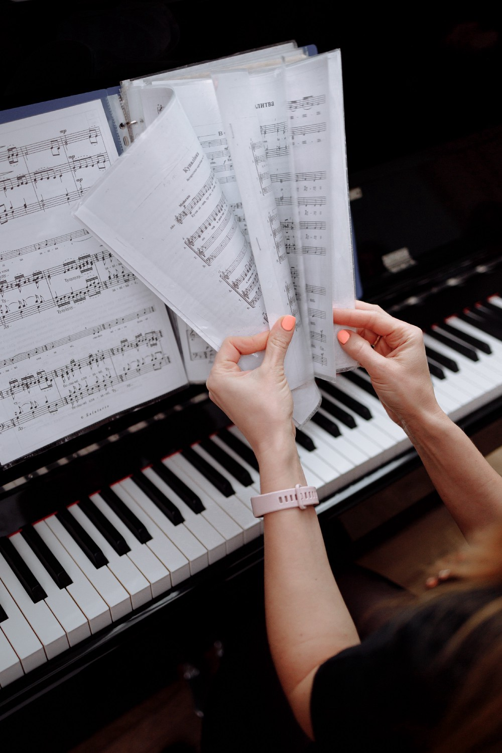 Woman's hands turn pages of sheet music over piano. Her hands appear to be of a person of color, and her fingers are topped with orange nail polish.
