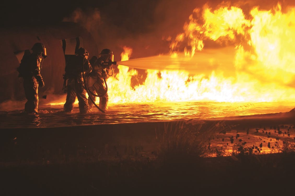 Firemen spraying water on a large fire
