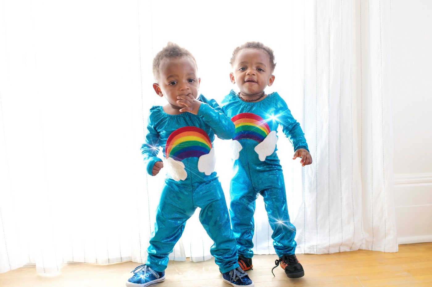 Two identical twin toddlers wearing matching outfits
