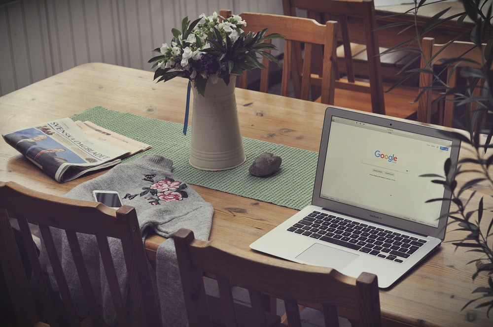 A flower vase and a laptop open to Google resting on a wood table.