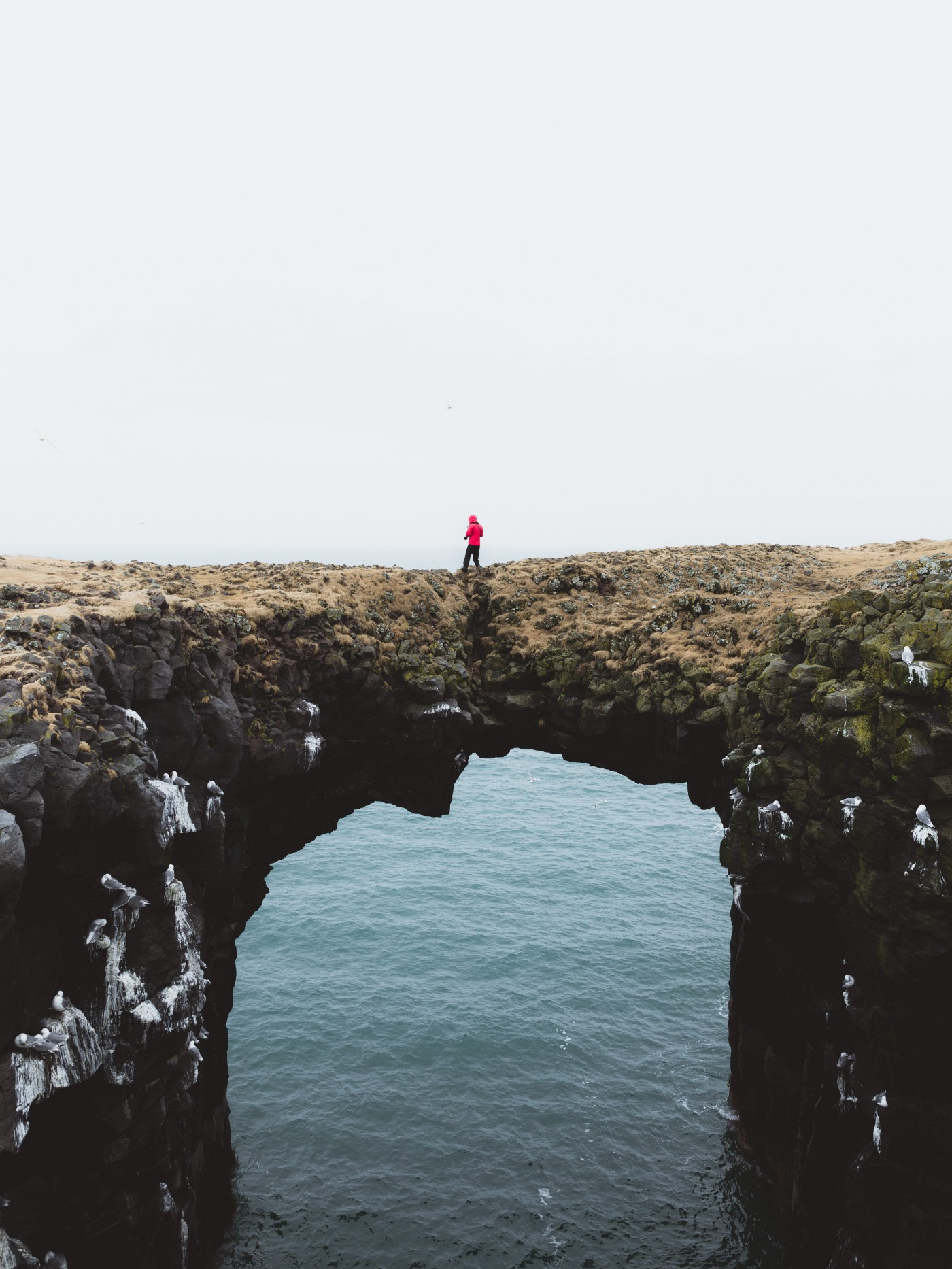 A person in a red rain jacket against a grey sky stands on jagged rocks spanning across water.