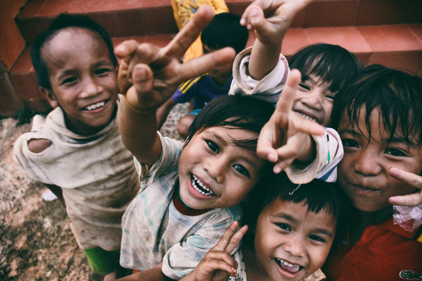 Several small children, dressed in stained and torn clothes, smile gleefully and put up peace signs.