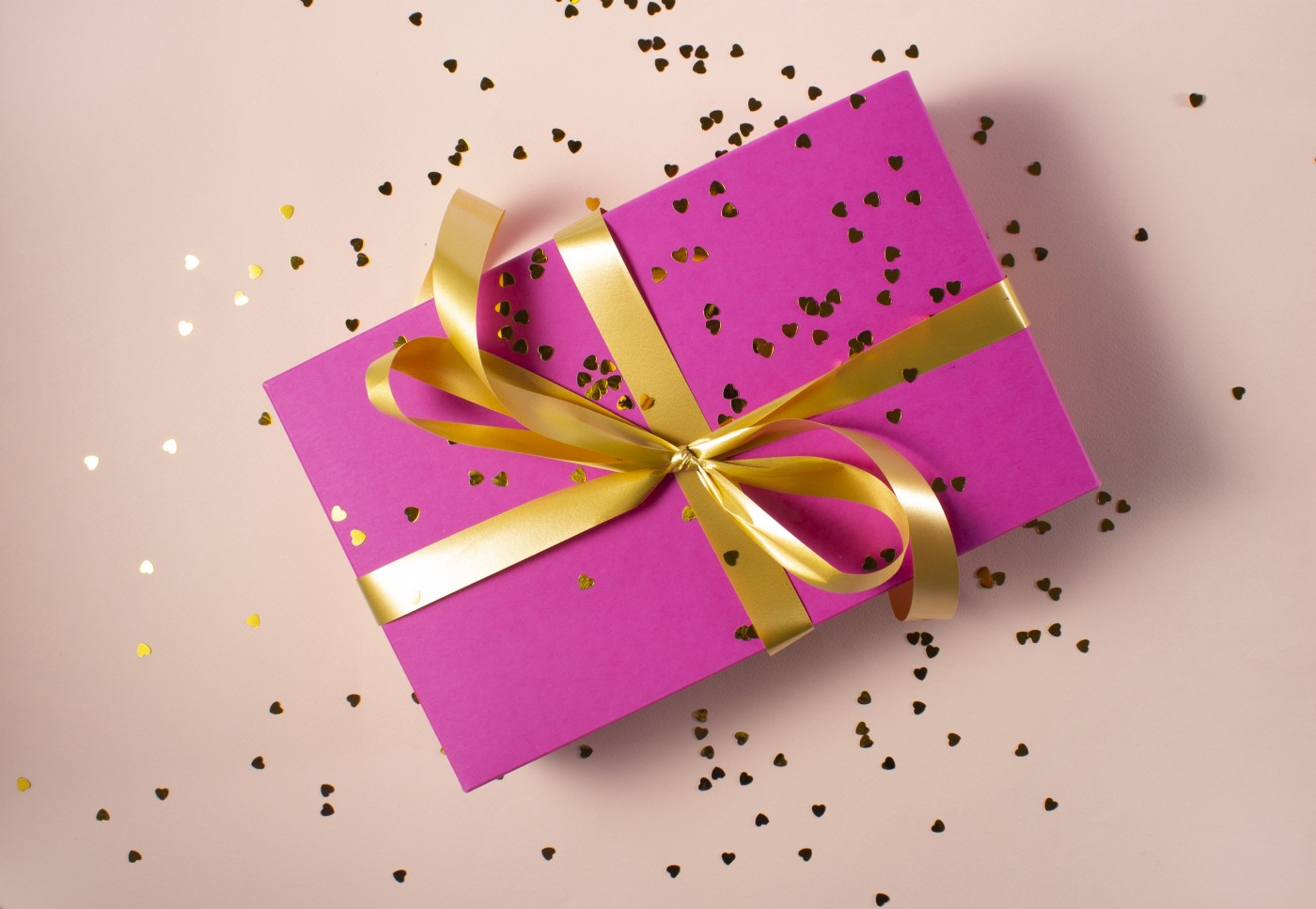 pink gift box with gold ribbon and glitter