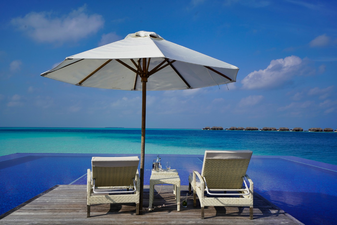 Two beach loungers on a desk, under a big white umbrella overlooking pristine blue waters.