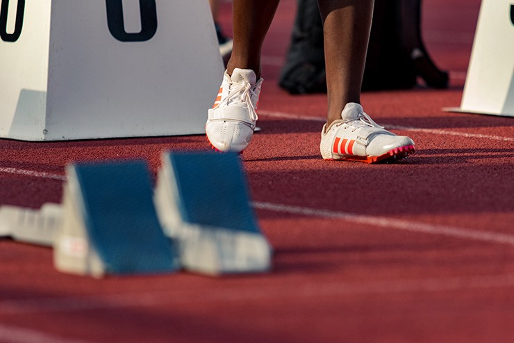 A sprinter's feet with the blocks in the foreground