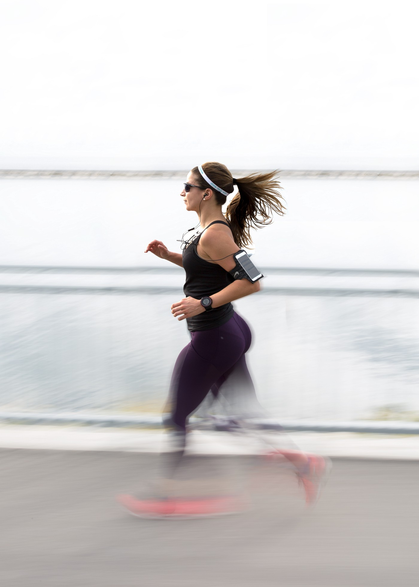 A photograph of a woman running alongside water, wearing sunglasses and a watch, with a phone strapped to her arm.