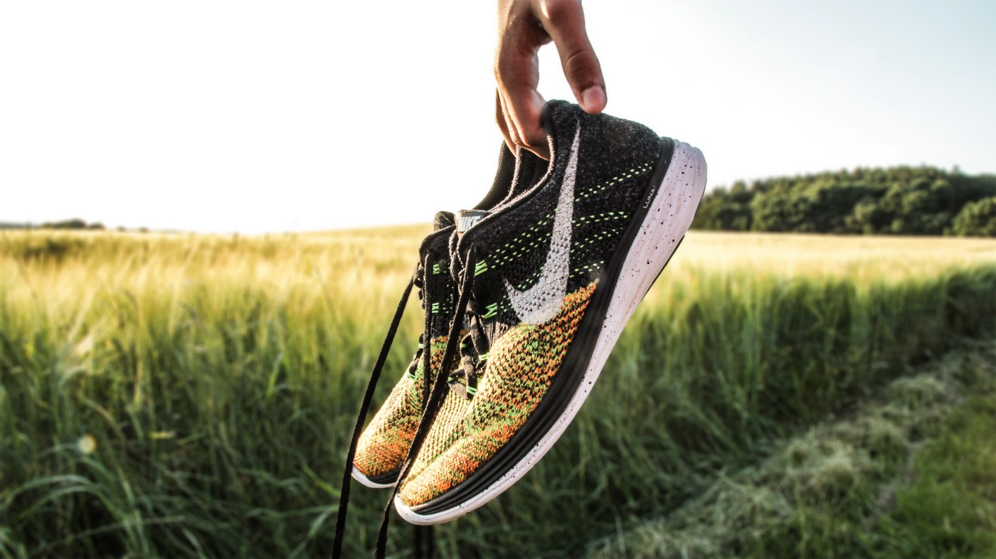 A person's hand holding pair of Nike running shoes with a field of wheat in background.