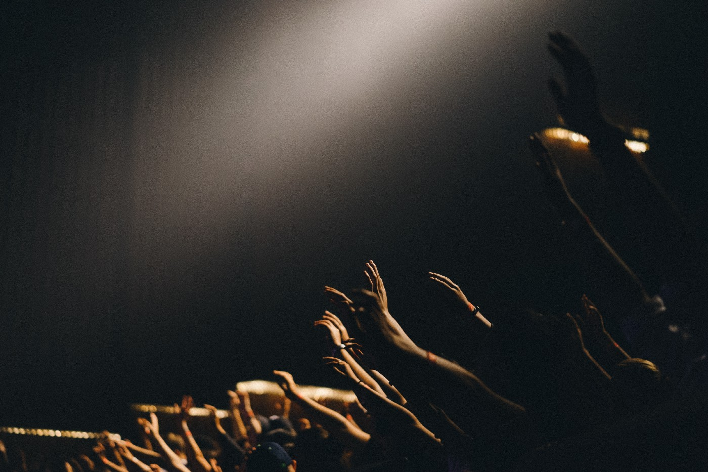 An image of many hands raised in the dark, with light touching their fingertips. They are worshiping, or perhaps begging.