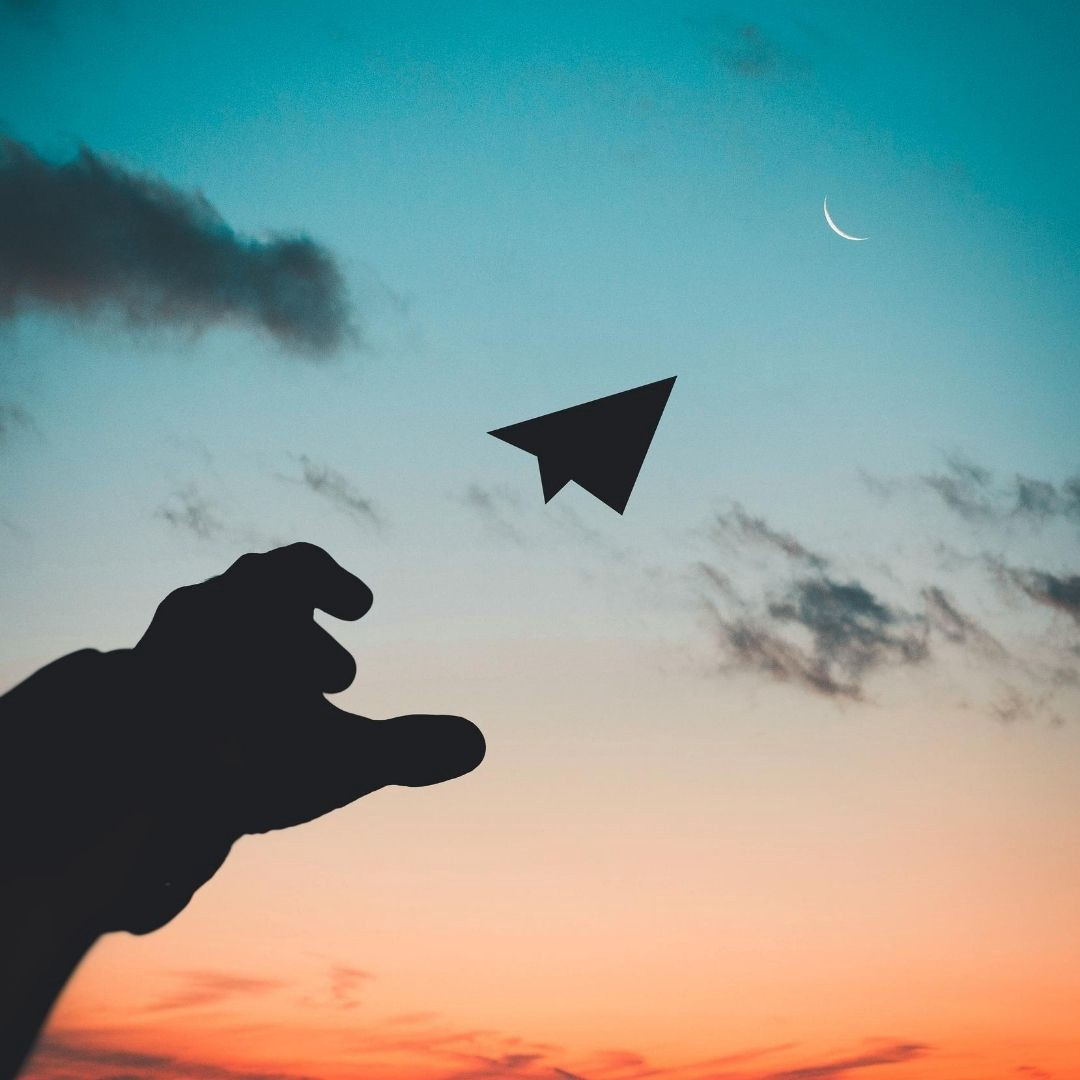 image of a hand throwing a paper airplane into the sky at dusk. Hand and airplane are black, sky is ombre teal to orange