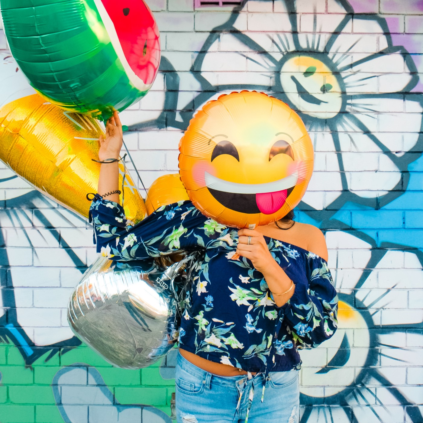 A girl with a smiley balloon covering her face