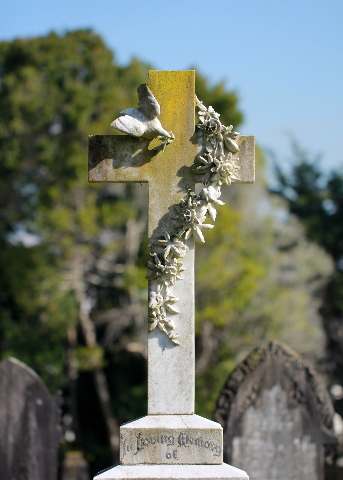 "A tombstone shaped like a cross with a dove and flowery garland wrapped around it. At the bottom reads ""in loving memory."""