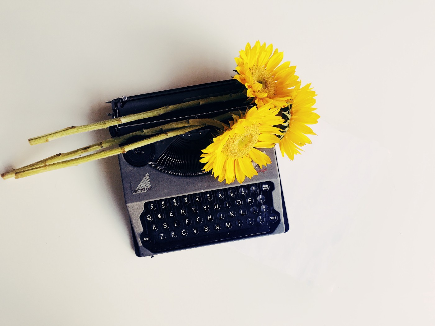 old-fashioned grey typewriter with yellow sunflowers on top