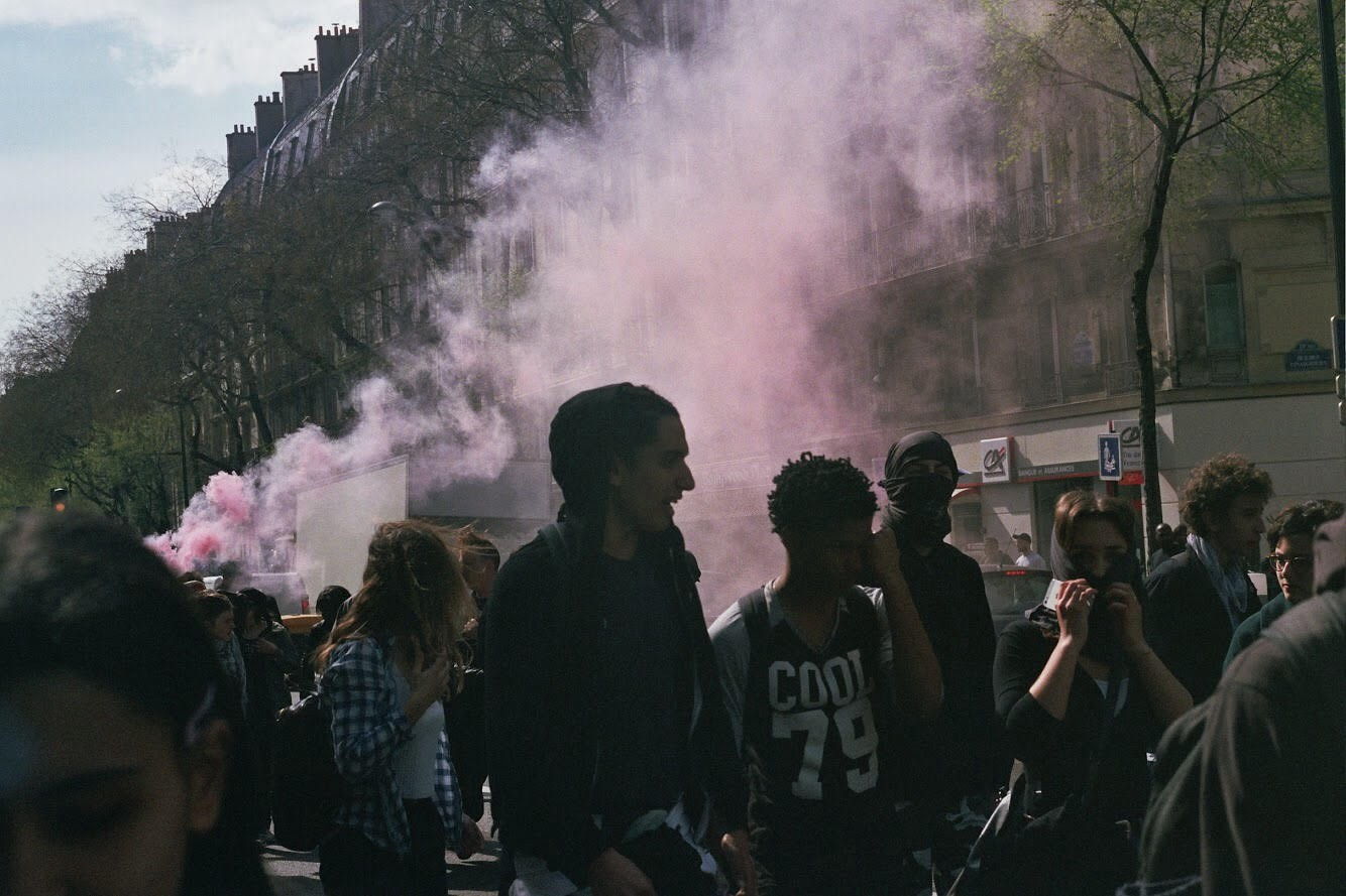Film photo of Paris during protest with people in foreground and purple smoke in background