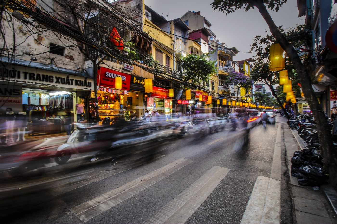Picture of a busy city with many business. It shows a crosswalk and all the cars are blurred as they circulate very fast.