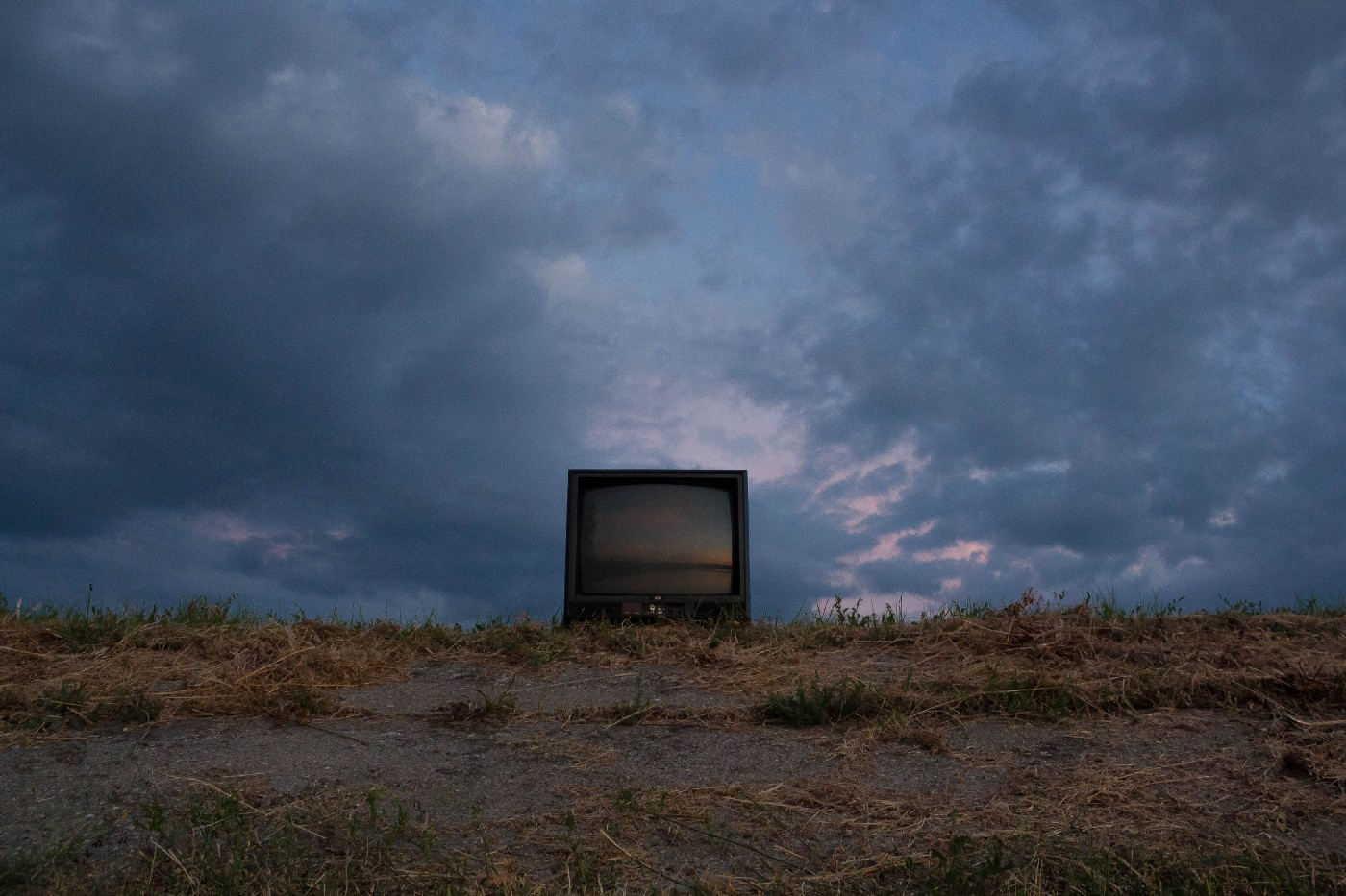 An old television left outdoors under a cloudy sky