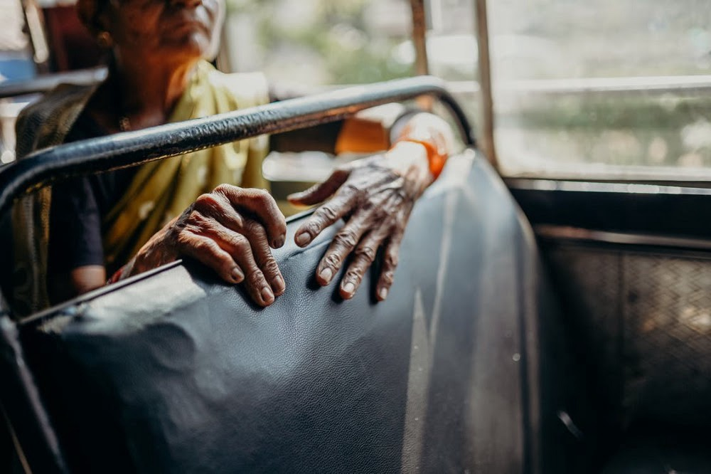 An old woman's hands clutch a bus seat