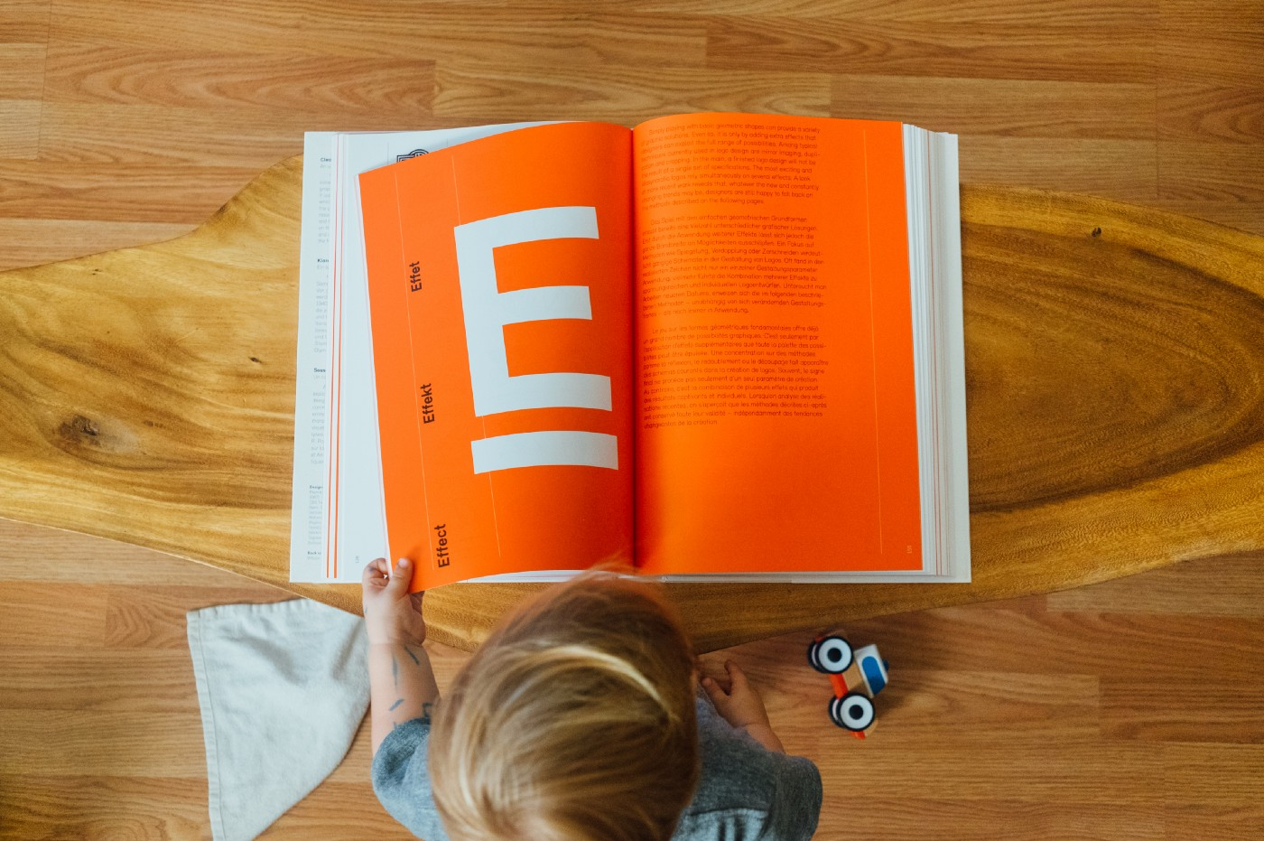 Little boy flipping through book with bright orange pages