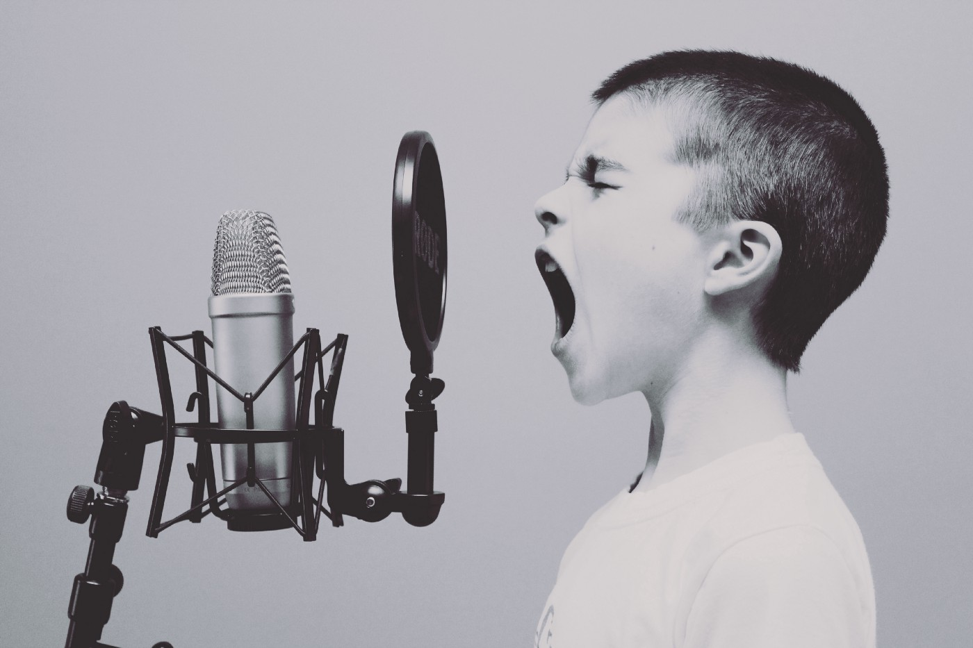 Boy singing or yelling into a microphone