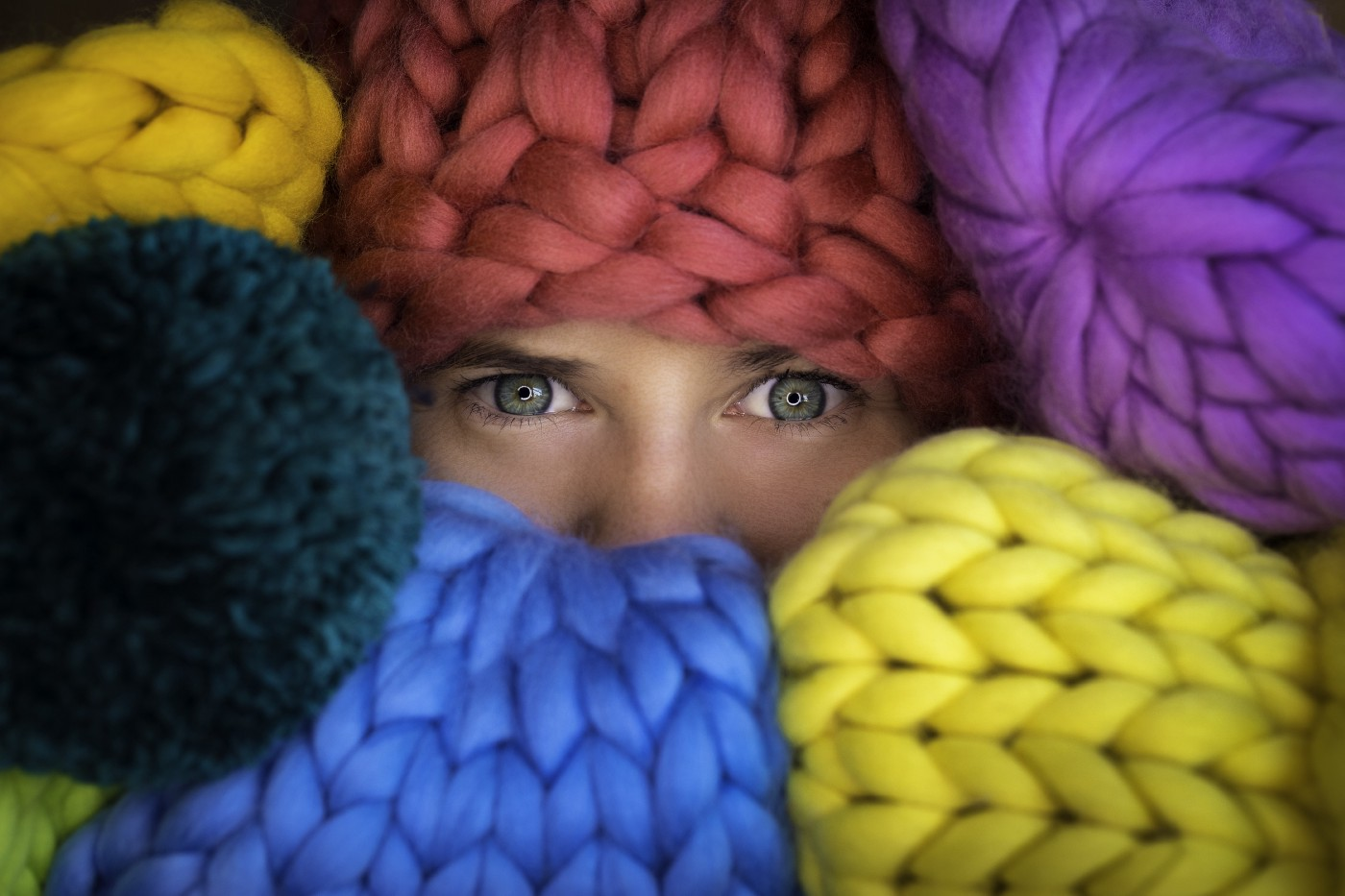 Picture of woman with balls of knitted material framing her blue eyes.