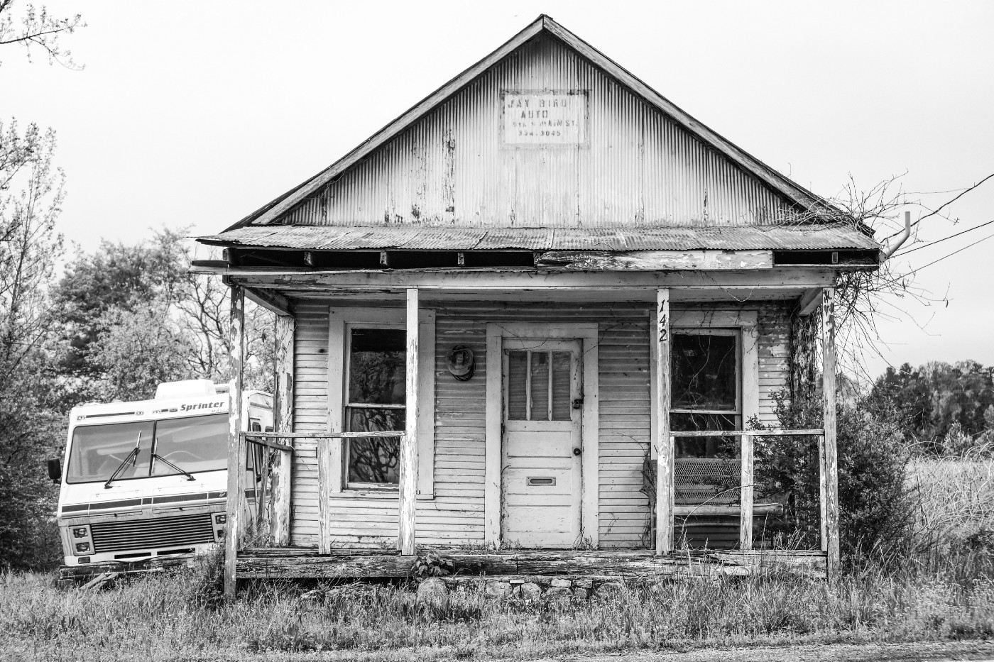 Old abandoned home black and with parked RV.