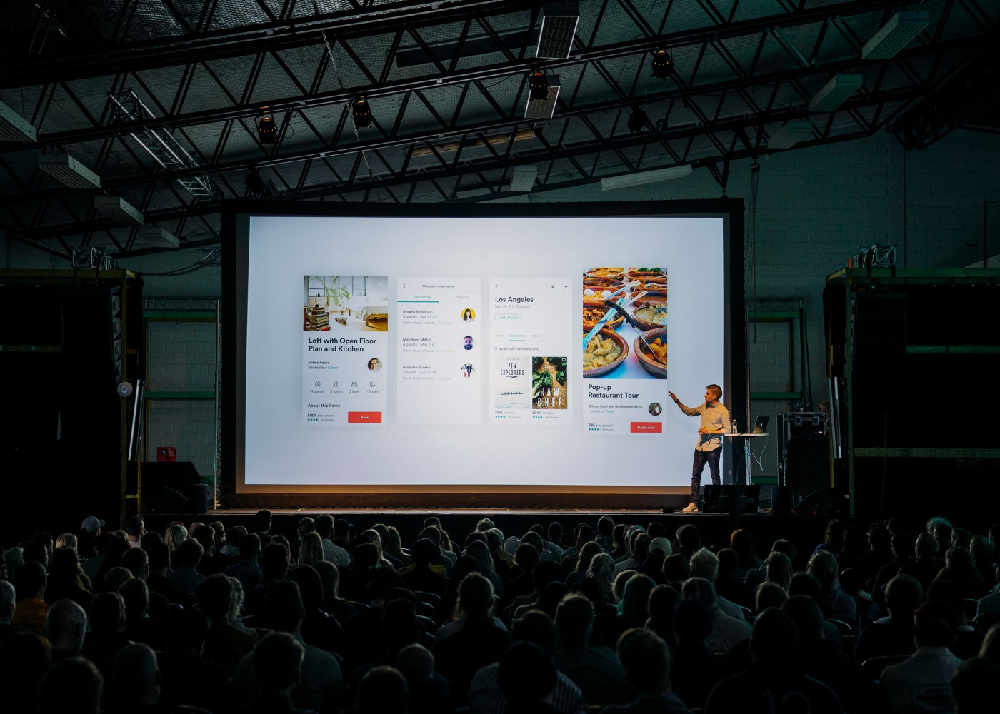Man giving a presentation to a large audience—the projector screen displays four screenshots from an app.