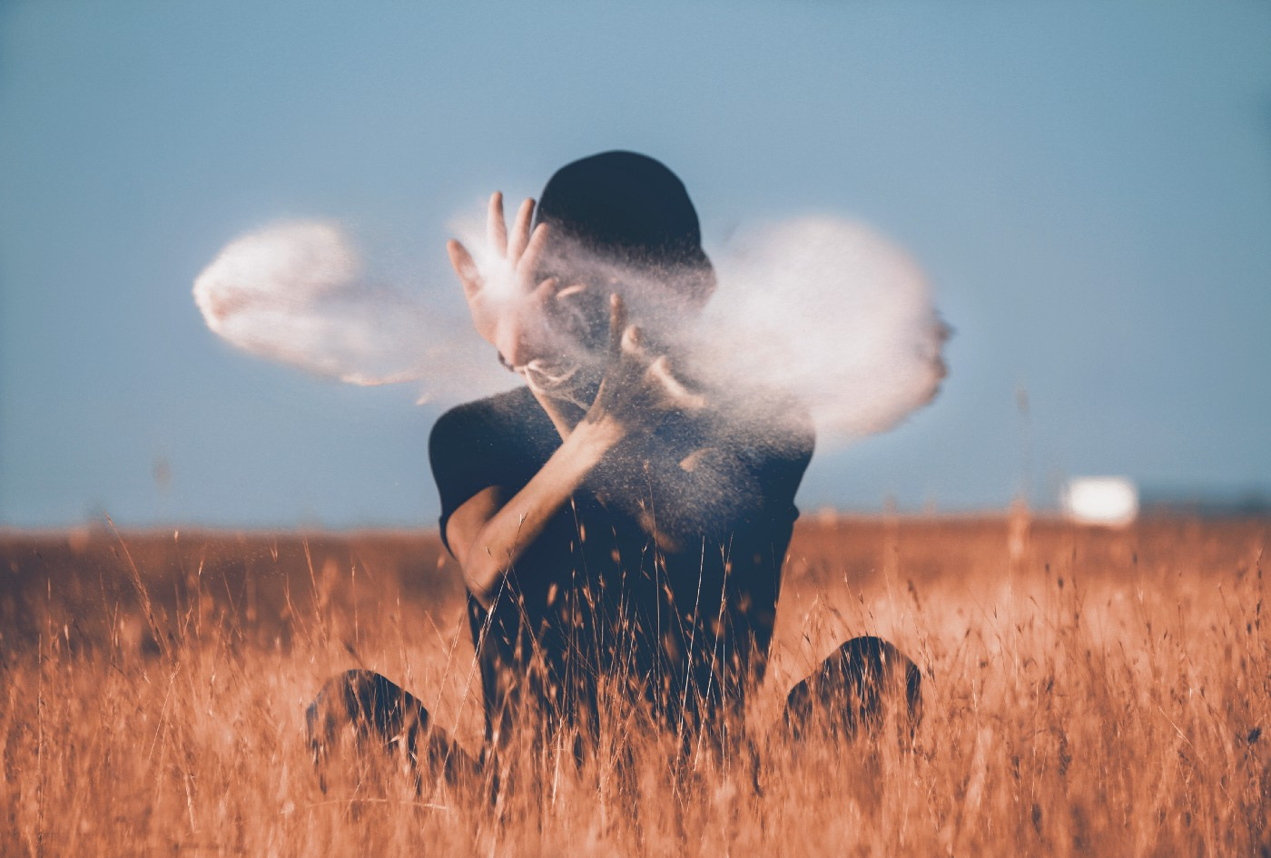 person whose face is obscured by a haze sitting in a wheat