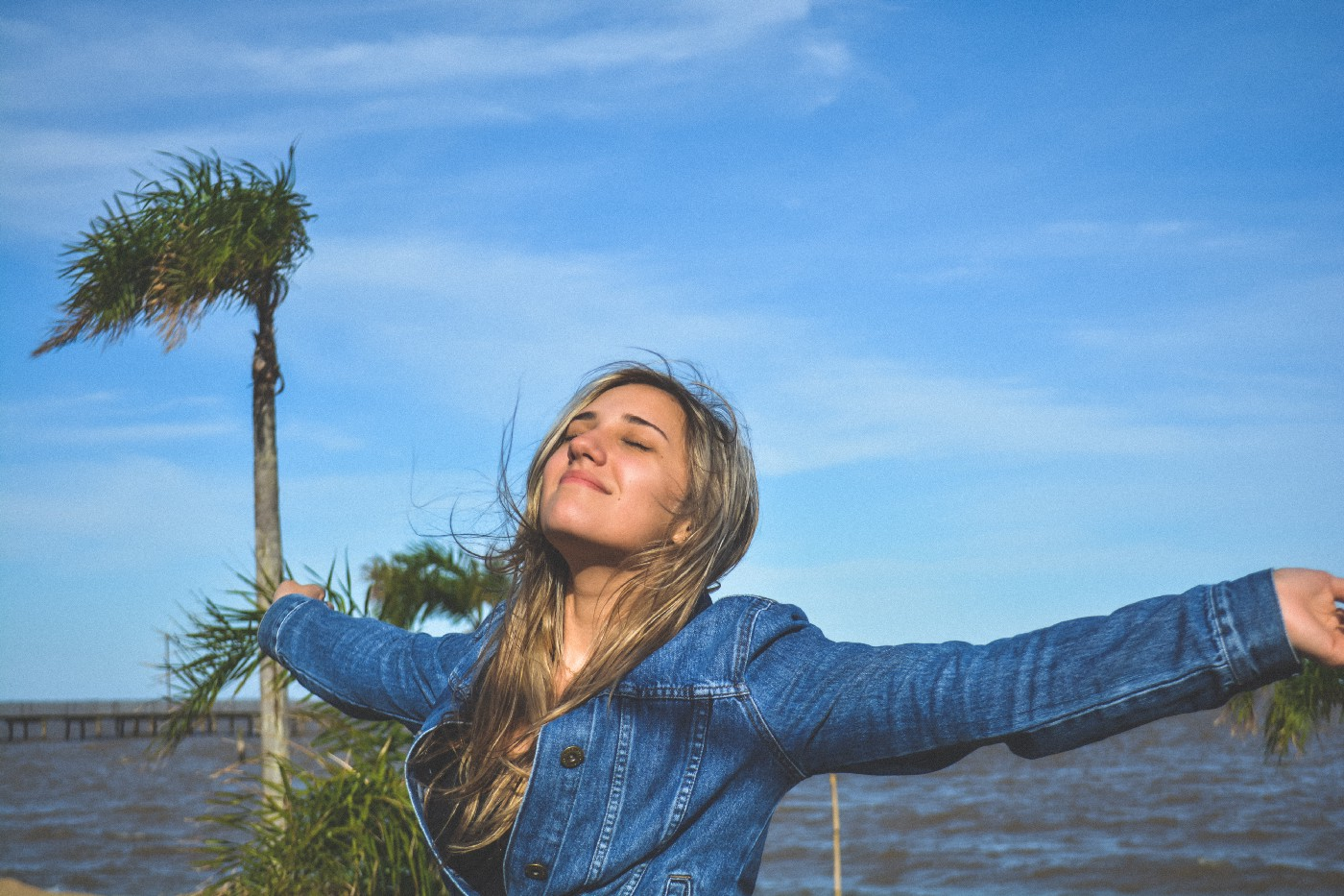 Woman standing with her arms outstretched, feeling happy and free.