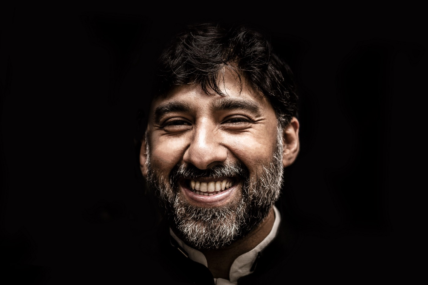 A potrait image of a man smiling in front of a dark background.