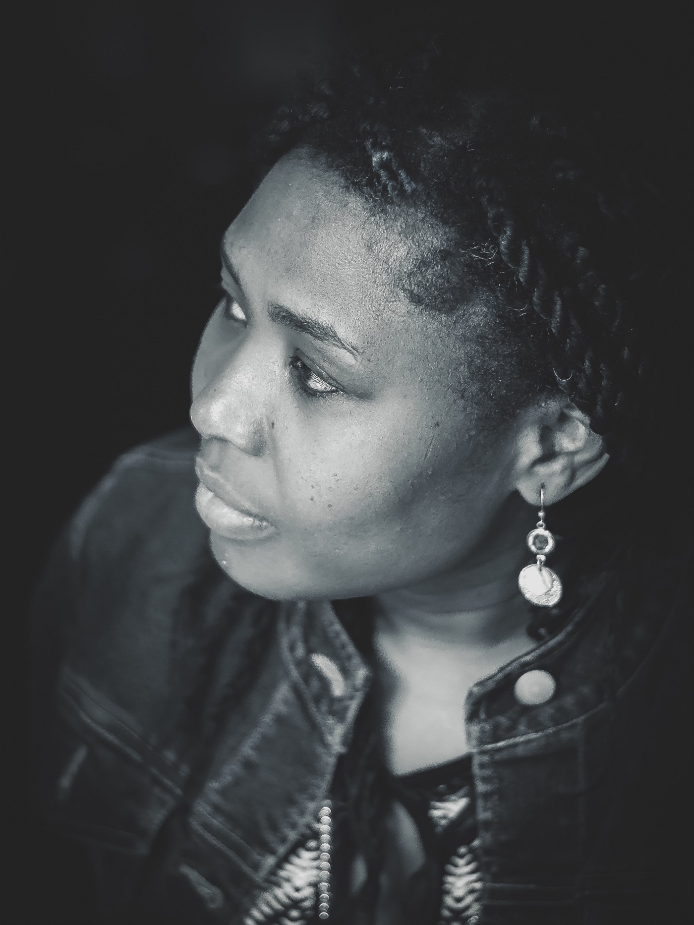 A side profile of an African woman wearing earrings and staring off into the distance in a dignified way.