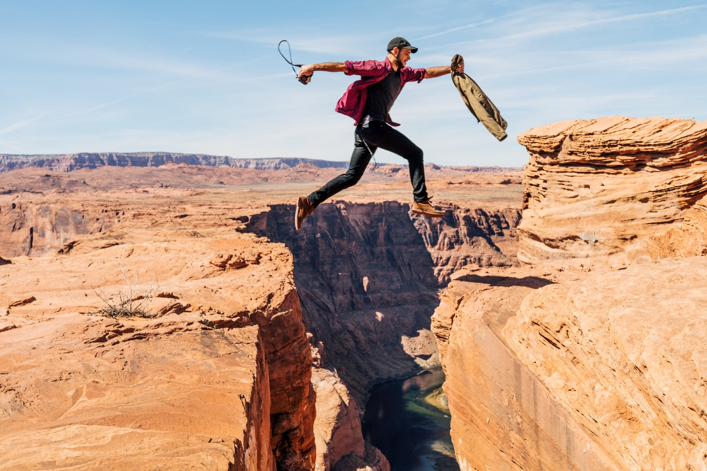 Man jumping over a cliff in the desert