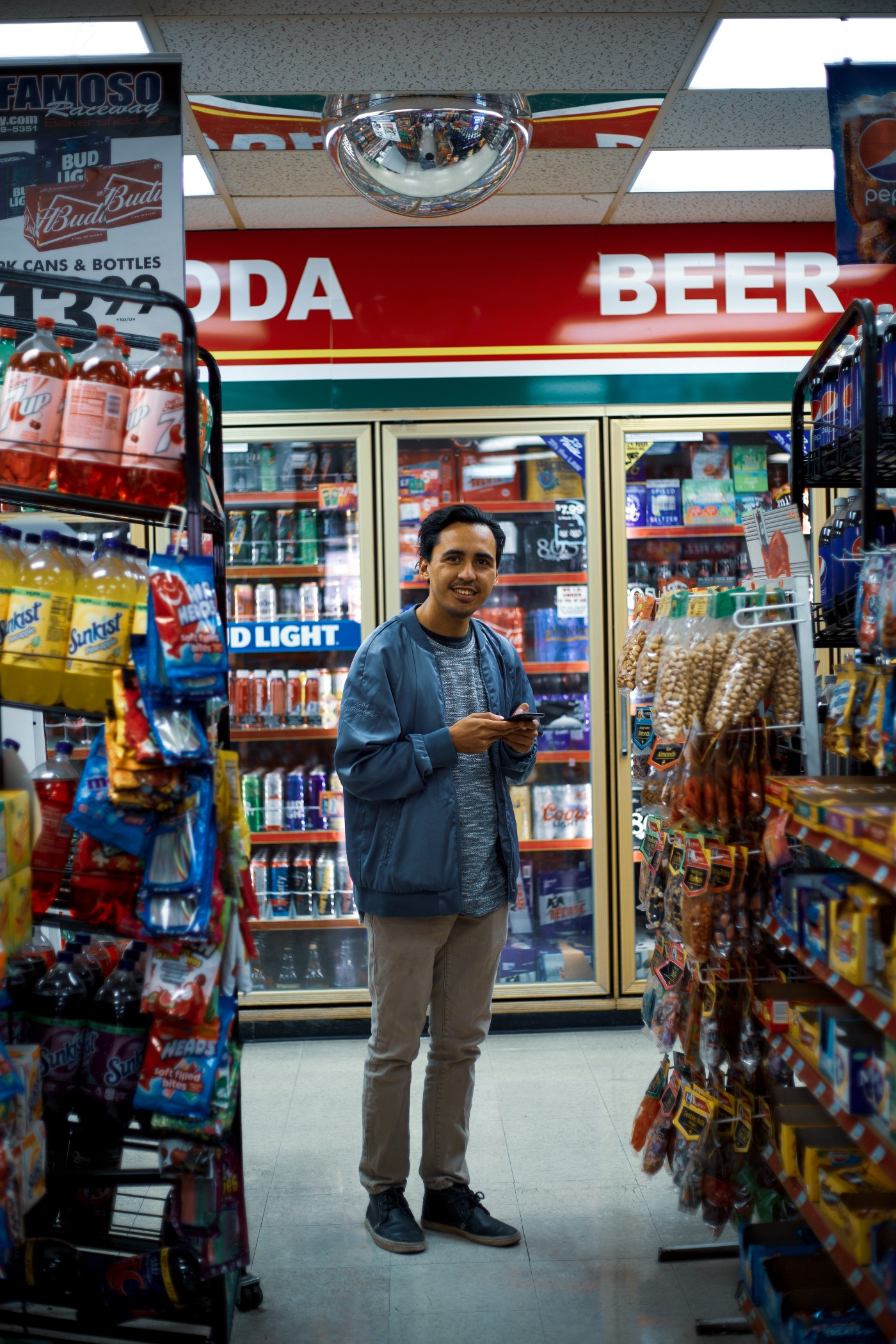 A man in a gas station smiling at the camera.