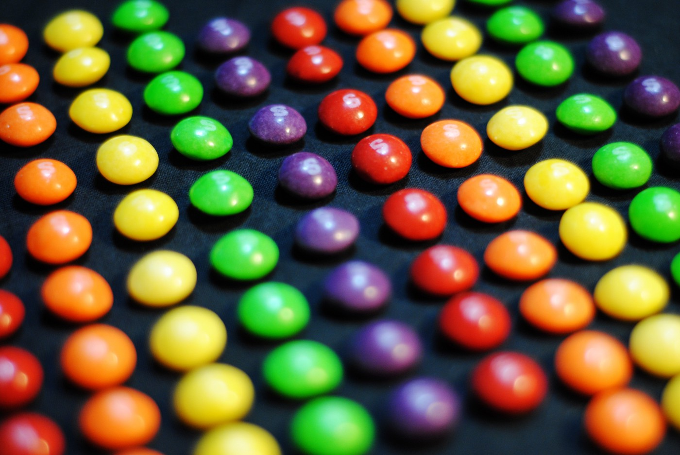 Neatly arranged lines of red, orange, yellow, green, and purple Skittles.