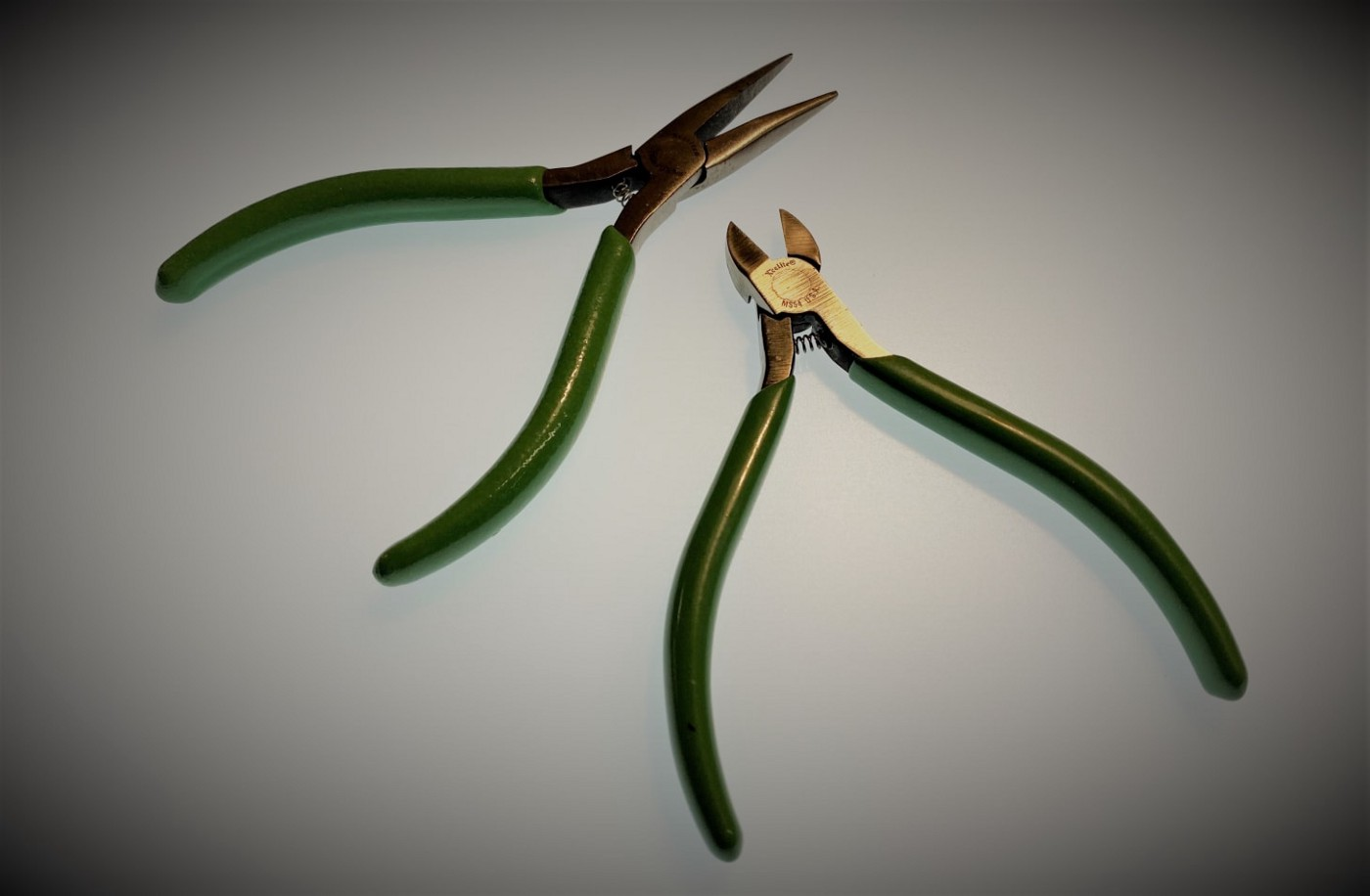 A small pair of green-handled needle-nose pliers and a pair of matching flush wire cutters, on a white background.