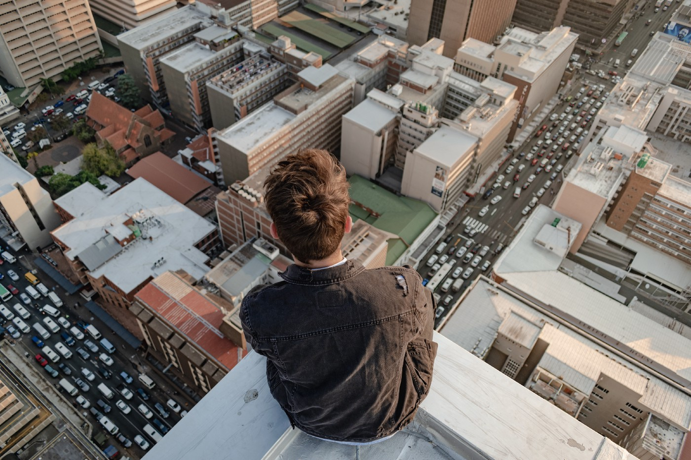 Person sitting on top of skyscraper looking at city