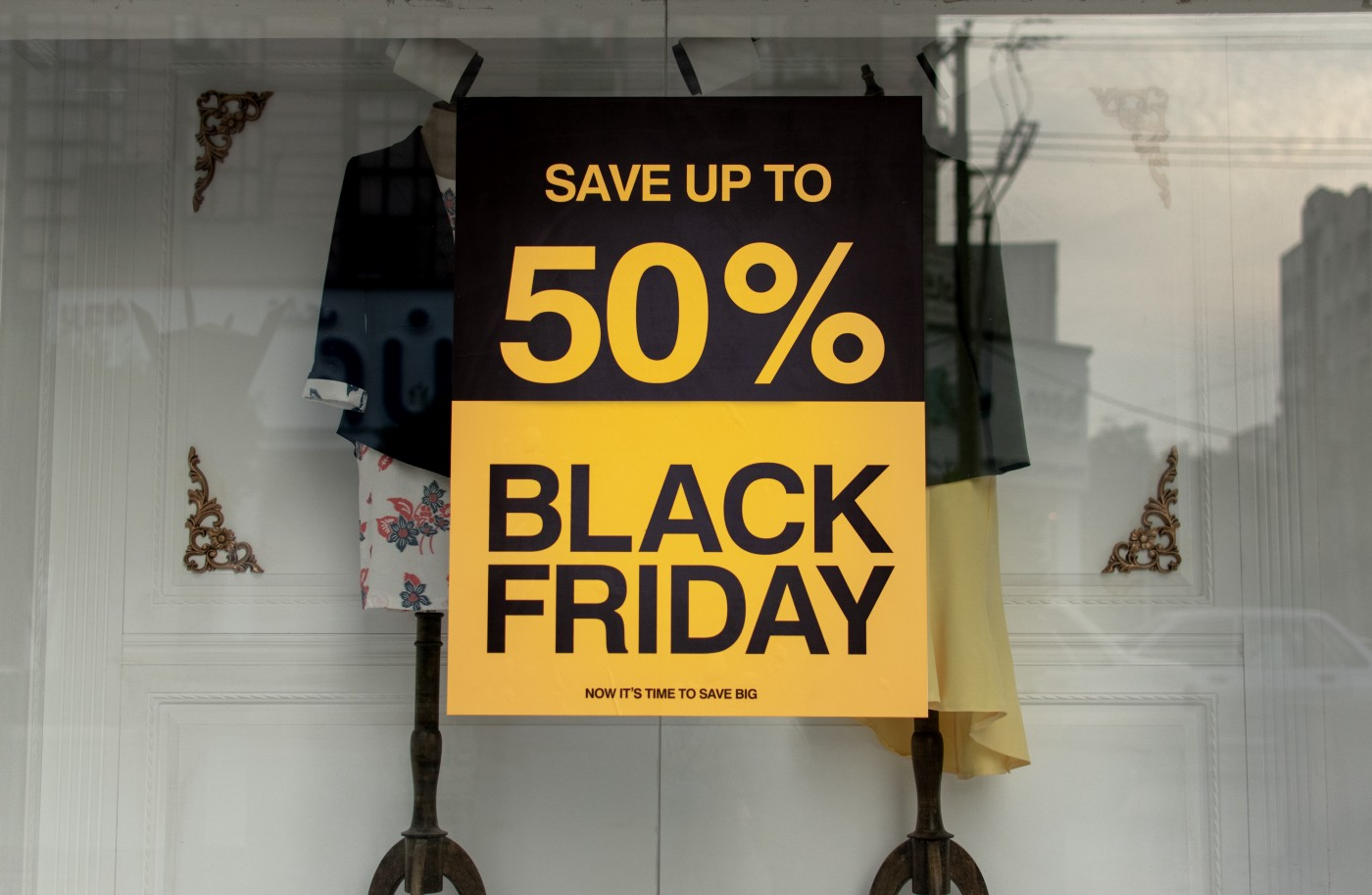 "A black and yellow sign posted in the window of a store that says ""Save up to 50% Black Friday Now it's time to save big"""