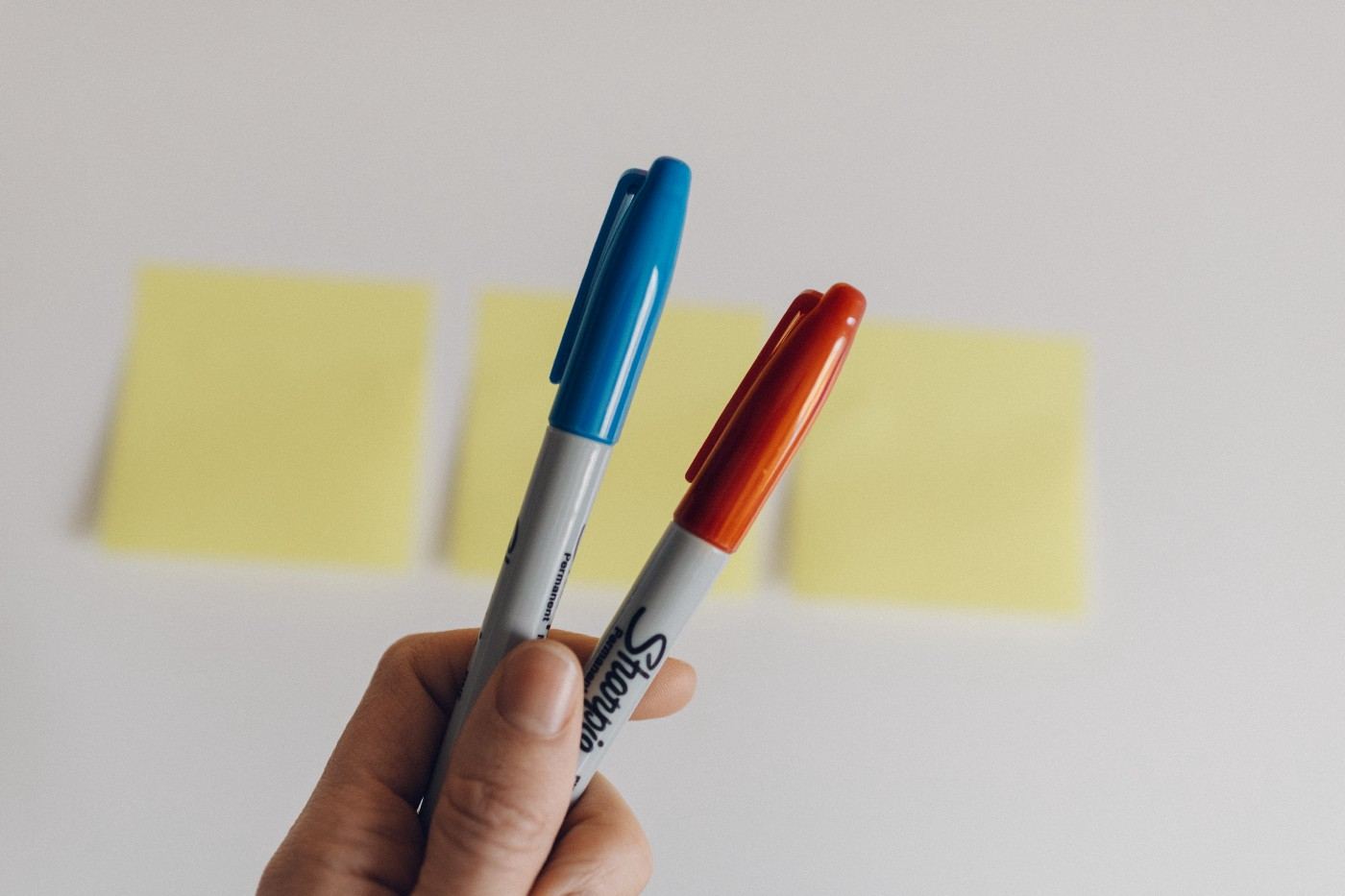 A blue and orange permanent marker is held up to camera in front of two post-it notes