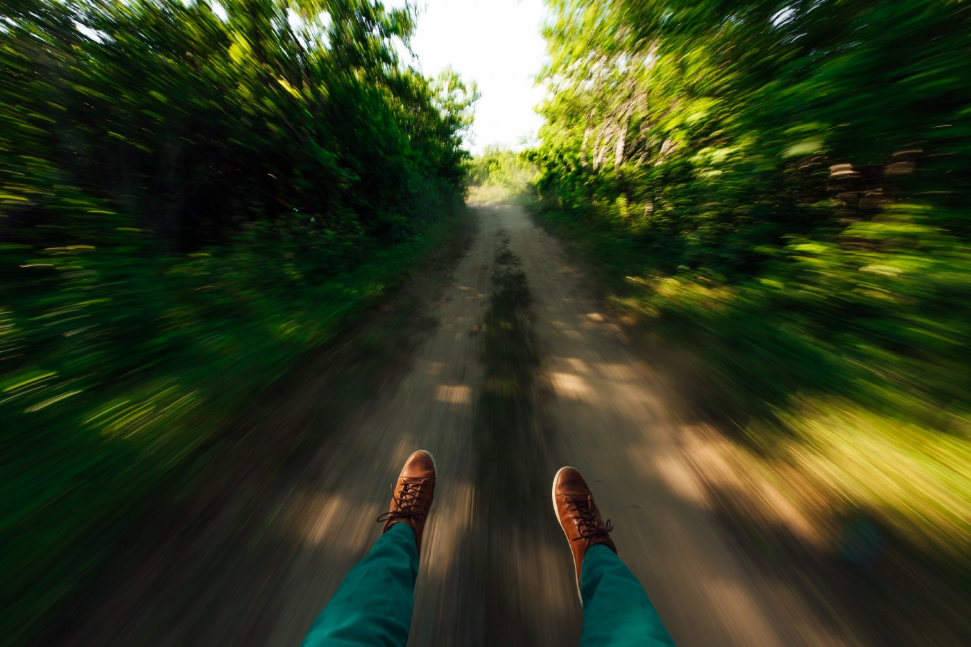 A man's feet as he slips swiftly down a path in the woods