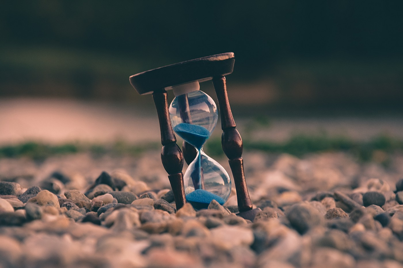 An hourglass sits among gravel as its sand pours from top to bottom.