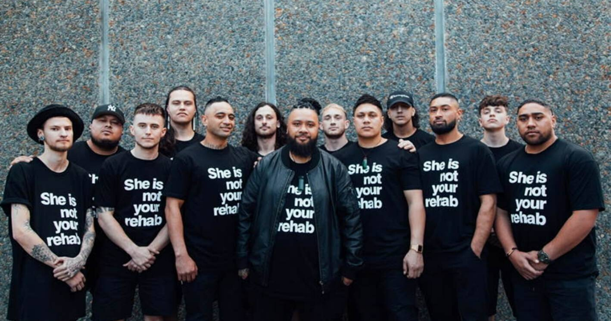 A photo of the Barbershop movement. A group of men wearing t-shirts that say, 'She is not your rehab'