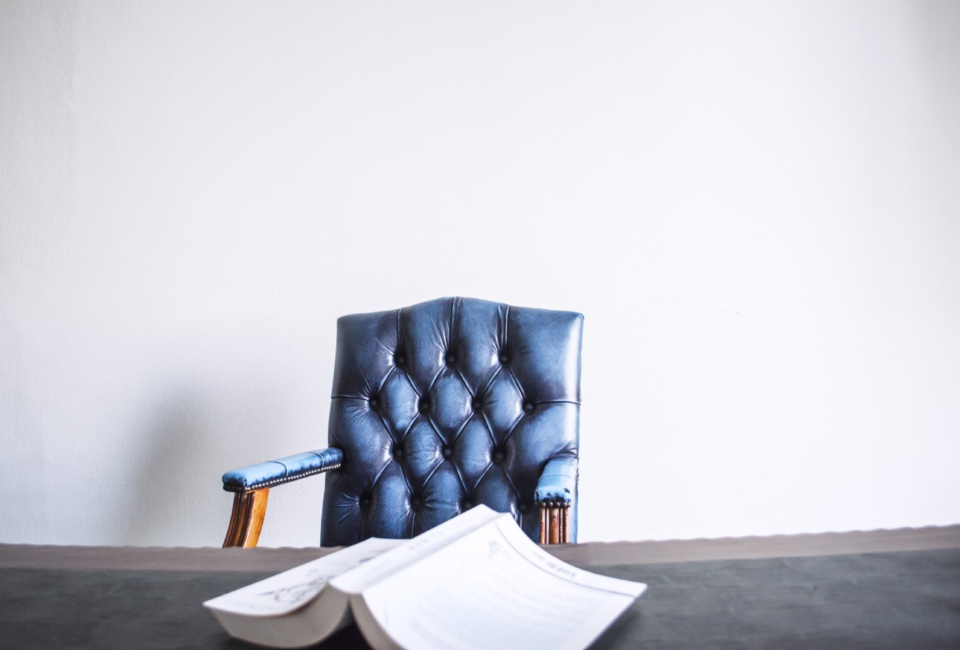 Opened book facing down on a desk in front of an empty blue leather chair