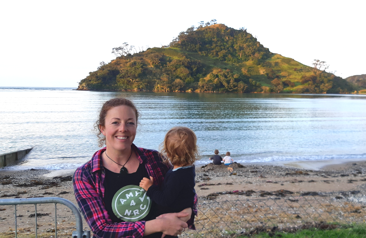 Amy holding her child at  a beach with the moana (sea) and a motu (island) behind them