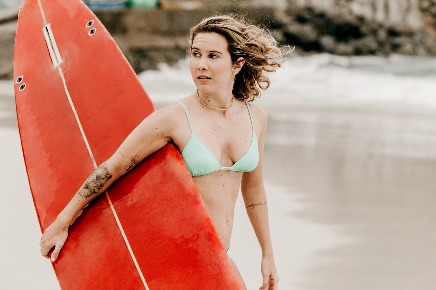 Girl holding a surfboard and wearing a bikini, looking nervous.