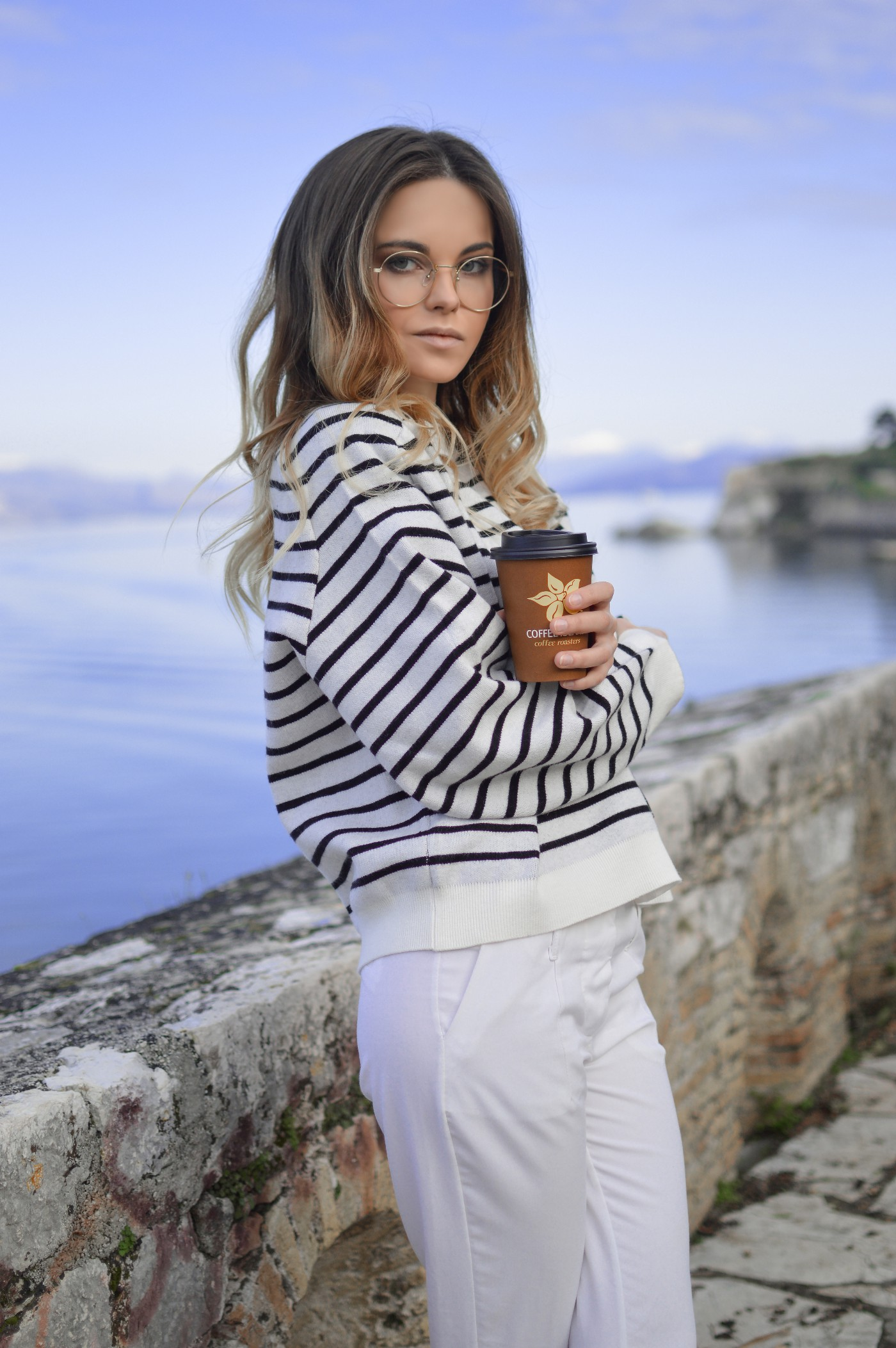 Dirty blonde White woman in a striped top and white pants holding a coffee cup