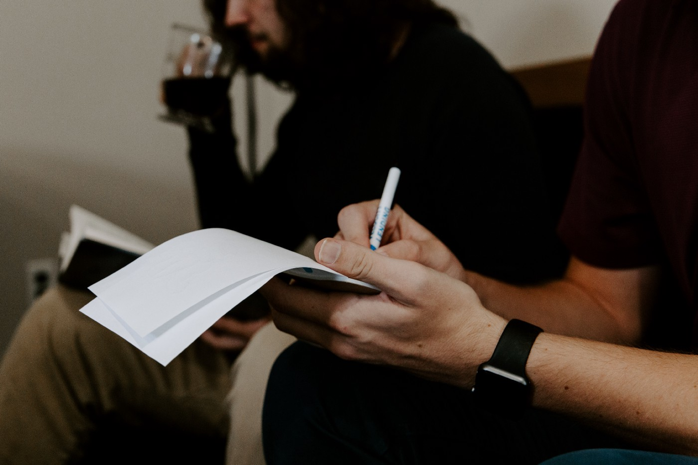 man writing in notebook listening