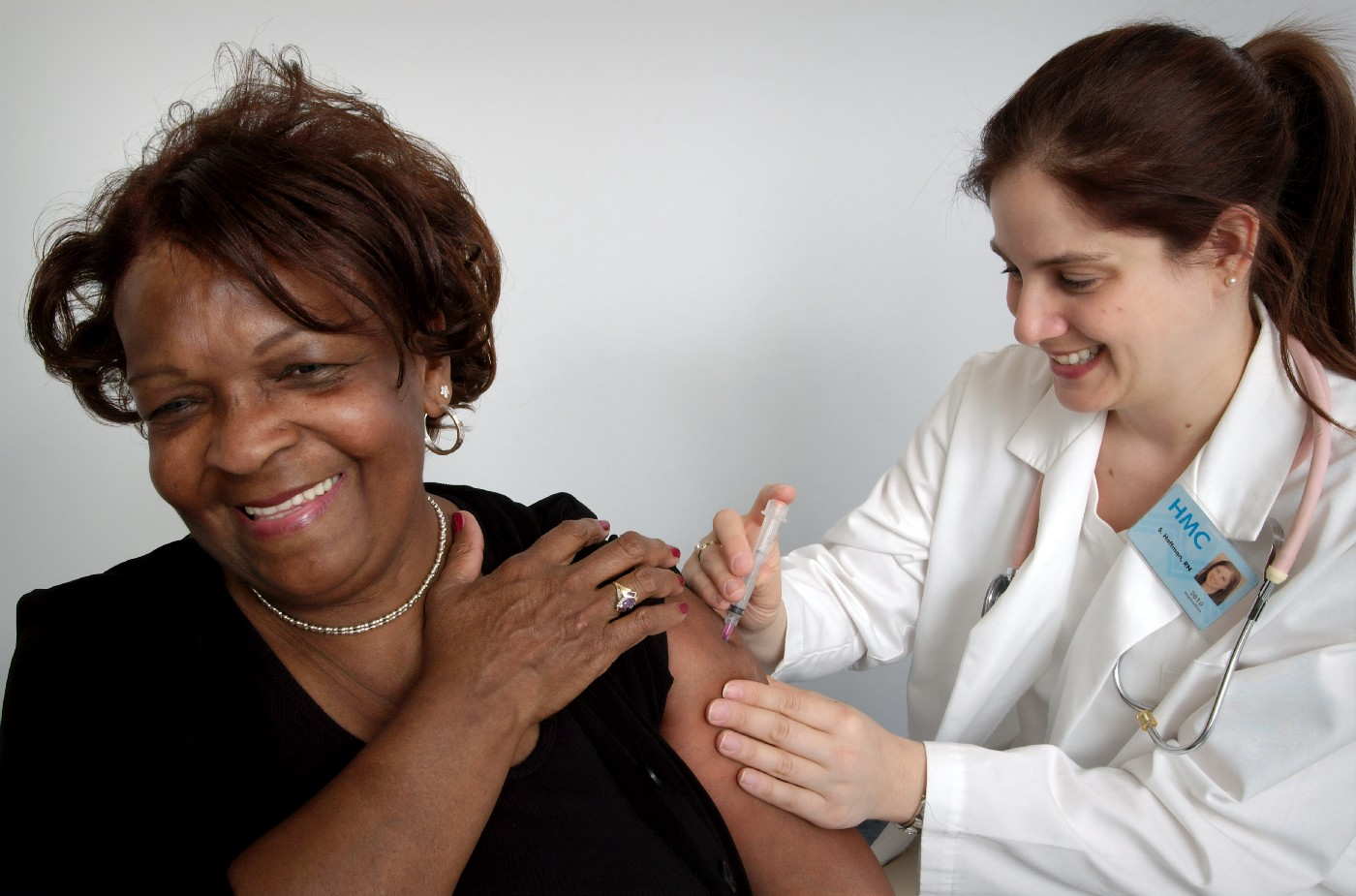 A healthcare professional administers a vaccine dose to a female patient.